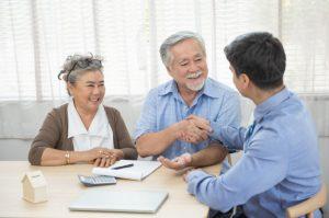 man giving handshake to old couple